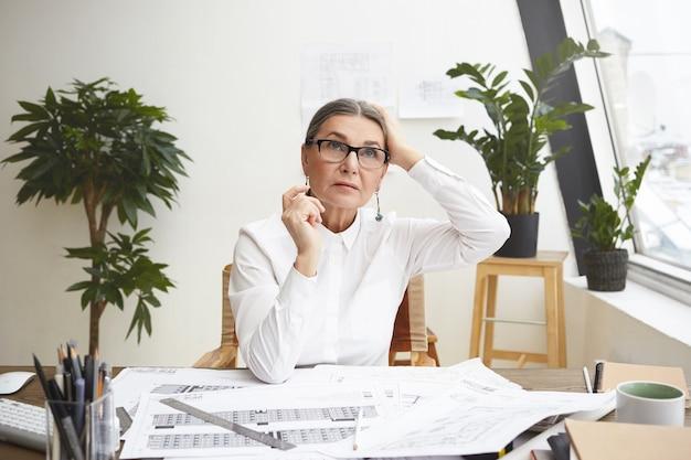 Portret van peinzende grijsharige vrouwelijke architect van in de vijftig die het hoofd aanraakt terwijl ze aan haar bureau werkt, tekeningen maakt met architectonische hulpmiddelen, opzoeken, op zoek gaat naar inspiratie