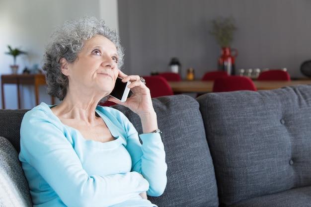 Portret van peinzende hogere vrouw die op mobiele telefoon spreekt