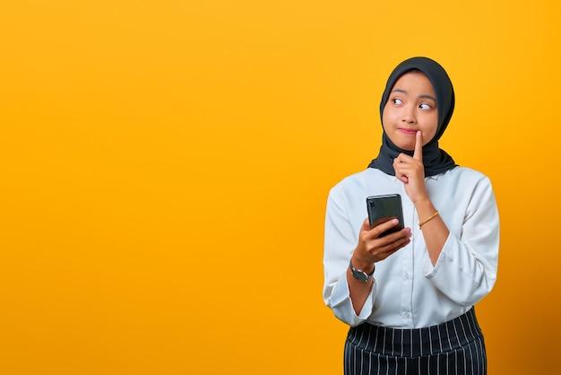 Portret van peinzende jonge aziatische vrouw met mobiele telefoon en hand op lippen op gele achtergrond