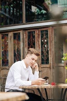 Portret van peinzende jongeman zittend aan tafel op terras, vriendin wachten en berichten in smartphone controleren
