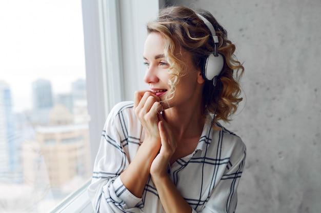 Portret van peinzende lachende vrouw luisteren muziek door oortelefoons, poseren in de buurt van venster close-up. modern stedelijk interieur.