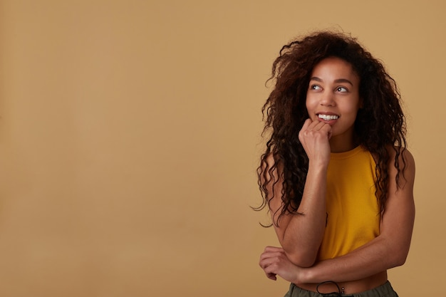 Portret van peinzende langharige krullende brunette dame die haar kin op opgeheven hand leunt en positief naar boven kijkt, geïsoleerd op beige