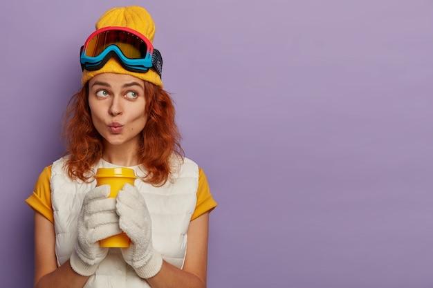 Portret van peinzende roodharige vrouw gekleed in vrijetijdskleding, houdt lippen rond, geniet van aromatische drank gwears beschermende bril op hoofd vormt binnen.