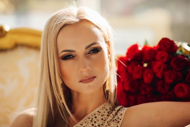 Portret van perfecte blonde dame met heldere oogmake-up die voorzijde met zonlicht bekijkt