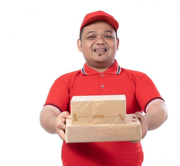 Portret van persoon die rode eenvormige levering vele dozen draagt