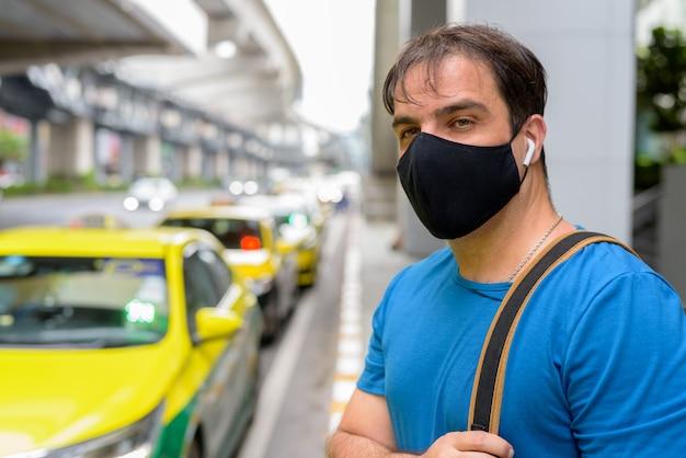 Portret van perzische toeristenmens met masker ter bescherming tegen uitbraak van het coronavirus bij het taxistation in de stad