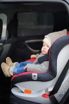 Portret van peuter jongen zit in autostoel