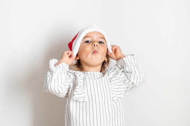 Portret van peutermeisje in rode hoed op kerstmis. verrassing concept