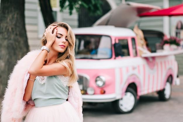 Portret van pin-up girl met roze bontstola op schouder op retro auto achtergrond. ze heeft lang blond haar, houdt haar hand op haar hoofd en kijkt naar beneden.