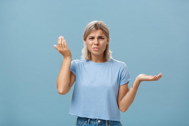 Portret van pissige en verwarde stijlvolle vriendin met blond haar die de palm hoog en opzij opheft met een verbijsterde uitdrukking die wordt ondervraagd en stomme onzin hoort over de blauwe muur