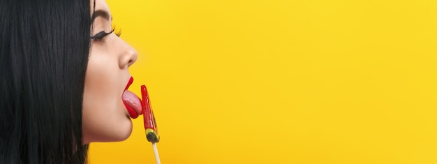 Portret van plus-groottemodel in profiel met lollyafbeelding op gele achtergrond