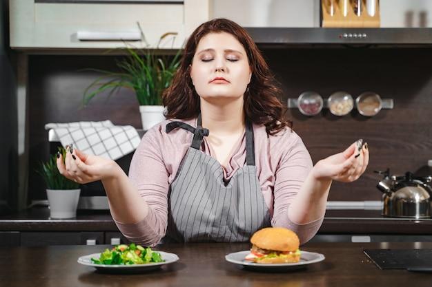 Portret van plus size vrouw met gesloten ogen mediteren kiezen tussen hamburger en salade in de keuken. wilskracht, gewichtsverlies en dieetconcept
