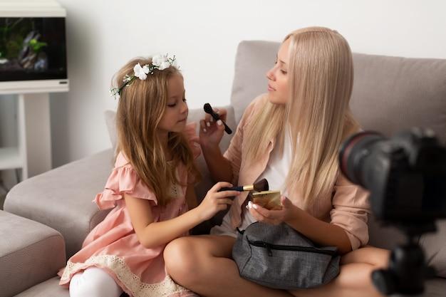 Portret van populaire jonge vrouw die make-up doet aan haar kleine dochter die in de spiegel kijkt en schoonheidsmiddel met een borstel toepast