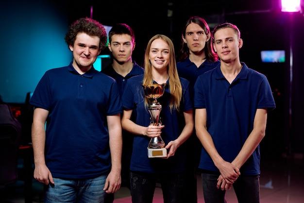 Portret van positief beste cybersportteam in blauwe t-shirts poseren met winnende prijs in computerclub