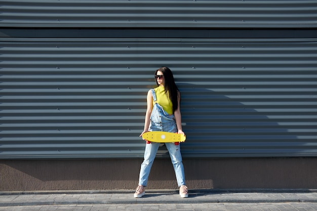 Portret van positief jong aantrekkelijk meisje die gele hoogste en jeans met geel skateboard dragen.