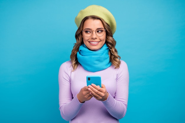 Portret van positief meisje gebruikt smartphone kijkt lege ruimte aan de zijkant op blauwgroen muur