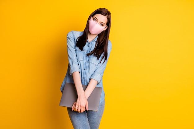 Portret van positief meisje met medisch masker houd laptop vast