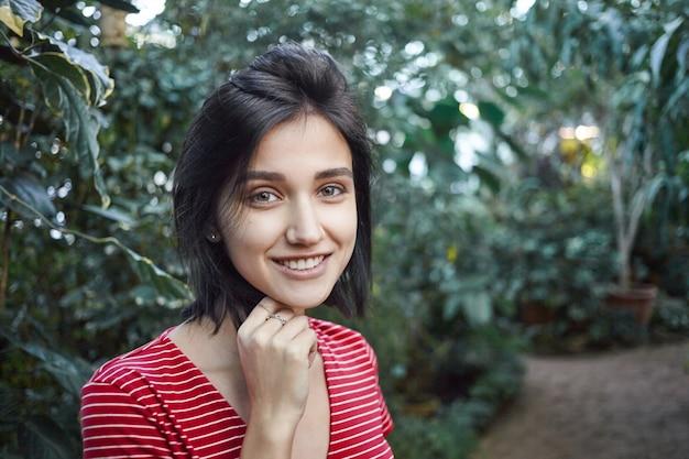 Portret van positief vriendelijk ogende jonge vrouwelijke plantkundige in vrijetijdskleding werken in kas, studeren verschillende exotische planten, gelukkig kijken, genieten van haar werk. natuur en milieu