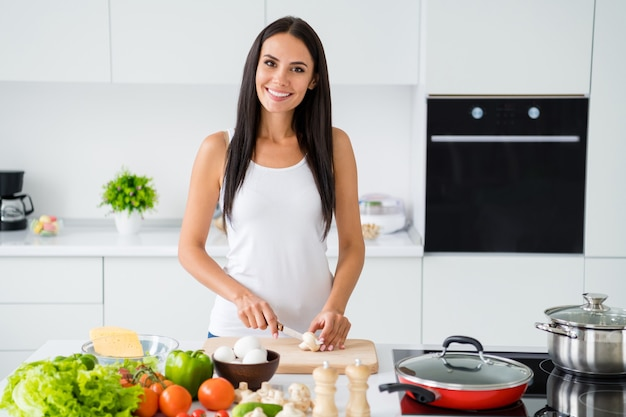 Portret van positief vrolijk bruin haar meisje gastronomisch dieet willen vegetarisch diner avondmaal gesneden markt champignons op hakken houten plank dragen witte singlet in keuken huis binnenshuis