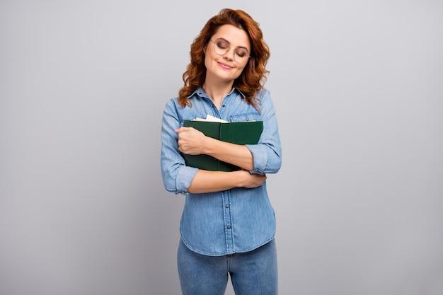 Portret van positief vrolijk dromerig meisje geniet van het lezen van papieren boekomhelzing omhels haar favoriete roman draag goede kleding geïsoleerd over grijze kleurmuur