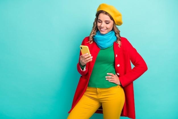 Portret van positief vrolijk meisje chillen gebruik mobiel lezen sociale media feedback draag groene trui broek broek hoofddeksel geïsoleerd over turquoise kleur achtergrond