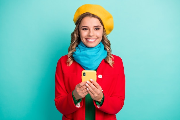 Portret van positief vrolijk meisje gebruik mobiele telefoon geniet van online sociale media communicatie post commentaar repost draag stijlvolle trendy bovenkleding geïsoleerd over turquoise kleur achtergrond