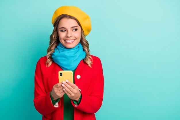 Portret van positief vrolijk meisje gebruik mobiele telefoon look copyspace geniet van post delen sociaal netwerk nieuws draag street style seizoen kleding geïsoleerd over groenblauw kleur achtergrond