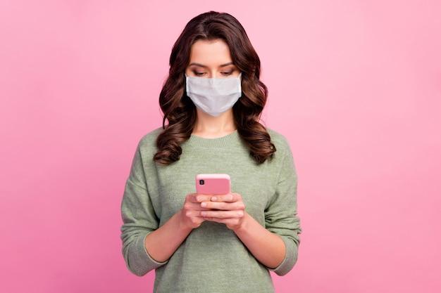 Portret van positief vrolijk meisje gebruik slimme telefoon lees delen repost sociaal netwerk covid nieuwigheden draag pullover jumper medisch masker trui geïsoleerd over pastelkleurige achtergrond
