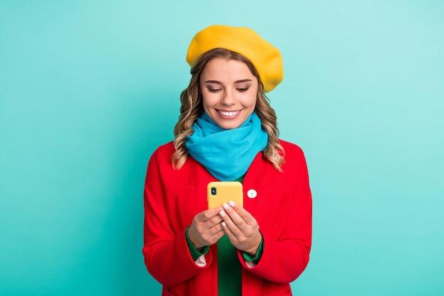 Portret van positief vrolijk meisje gebruik smartphone repost delen abonneer sociaal netwerk nieuws draag heldere stijlvolle streetstyle kleding geïsoleerd over groenblauw kleur achtergrond