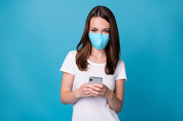 Portret van positief vrolijk meisje gebruik smartphone volg post commentaar sociale media covid nieuws draag goed uitziende medische maskerkleren geïsoleerde blauwe kleur achtergrond