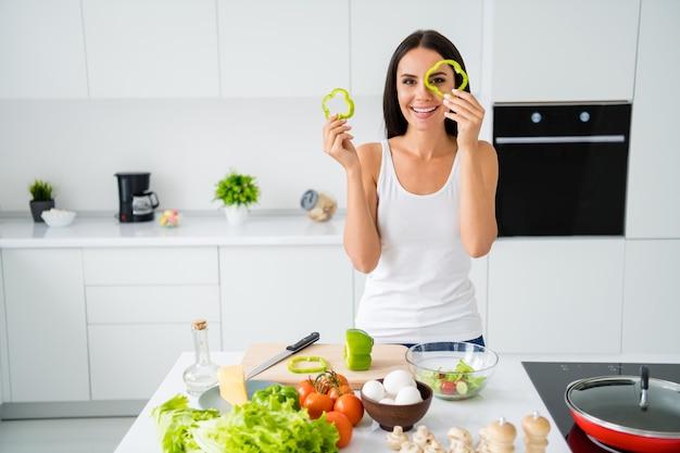 Portret van positief vrolijk meisje huisvrouw wil chef-kok vegetarische lunch bereiden houden peper plakjes stel je voor dat het haar bril is, draag wit hemd in keukenhuis binnenshuis