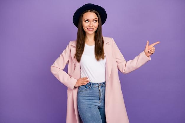 Portret van positief vrolijk meisje in pastel jas kleding wijs wijsvinger copyspace aangeven advertenties promo directe manier draag moderne herfst outfit geïsoleerd over violet kleur achtergrond