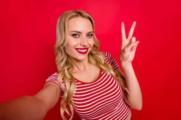 Portret van positief vrolijk meisje maakt selfie v-teken