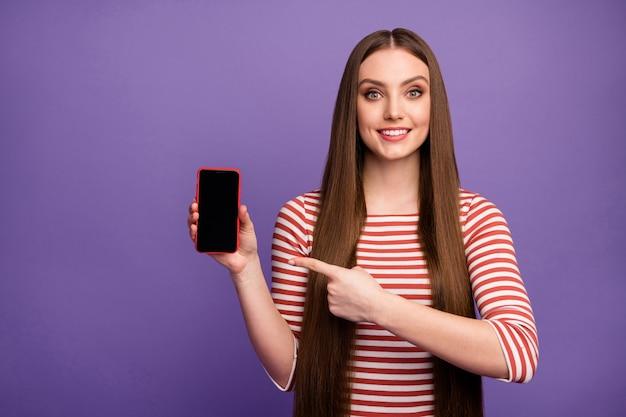 Portret van positief vrolijk meisje promotor houd mobiel punt wijsvinger adviseren kies nieuwe moderne technologie aanbod dragen witte trui geïsoleerd over violette kleur muur