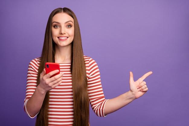 Portret van positief zelfverzekerd meisje promotor gebruik smartphone aangeven sociale netwerkadvertenties promo punt wijsvinger copyspace slijtage trui geïsoleerd over paarse kleur muur