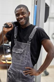 Portret van positieve afro amerikaanse automonteur in uniform poseren na het werk