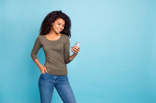 Portret van positieve afro-amerikaanse meid blogger gebruikt haar smartphone lees feednews in haar blog sociale media-account draag stijlvolle groene trui denim jeans geïsoleerd over blauwe kleur muur