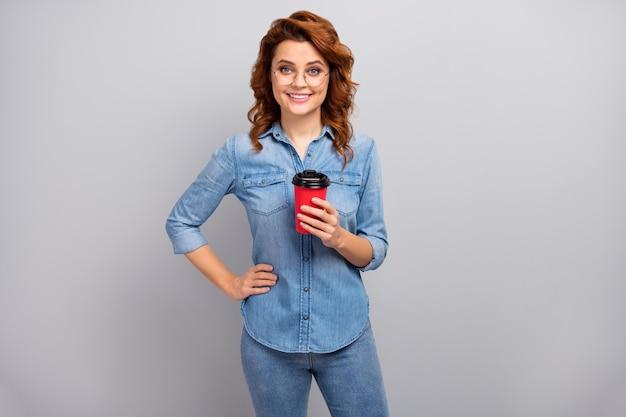 Portret van positieve charmante mooie slimme succesvolle universiteitsmedewerker rust ontspannen houden warme cappuccino drank dragen goede look outfit geïsoleerd over grijze kleur muur