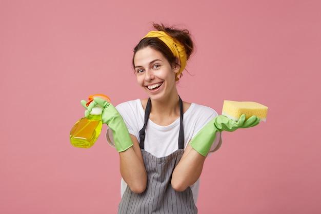 Portret van positieve emotionele jonge europese vrouw met vrolijke gelukkige glimlach die het algemene schoonmaken doet