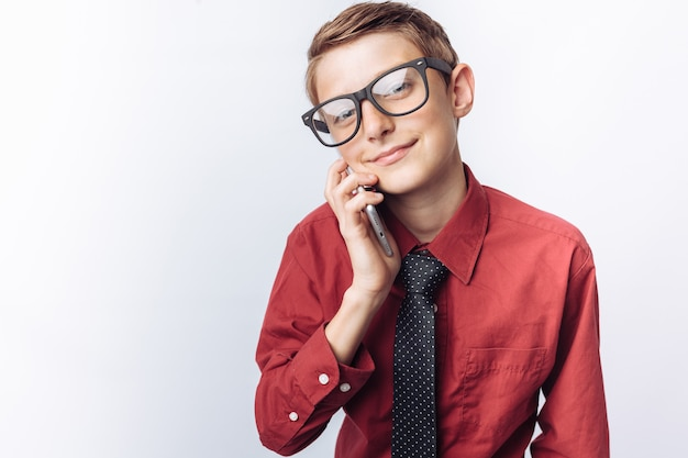 Portret van positieve en emotionele schooljongen praten over de telefoon