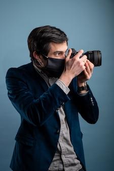 Portret van positieve fotograaf, man met medisch masker met professionele digitale dslr-camera.