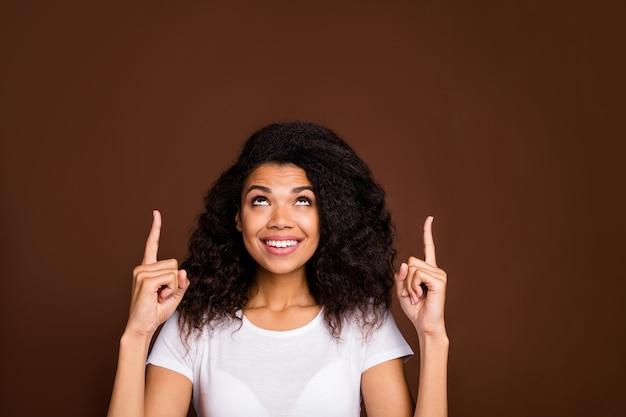 Portret van positieve funky afro amerikaanse meisje promotor close-up wijsvinger copyspace sekte suggereren advertenties promo dragen wit t-shirt.