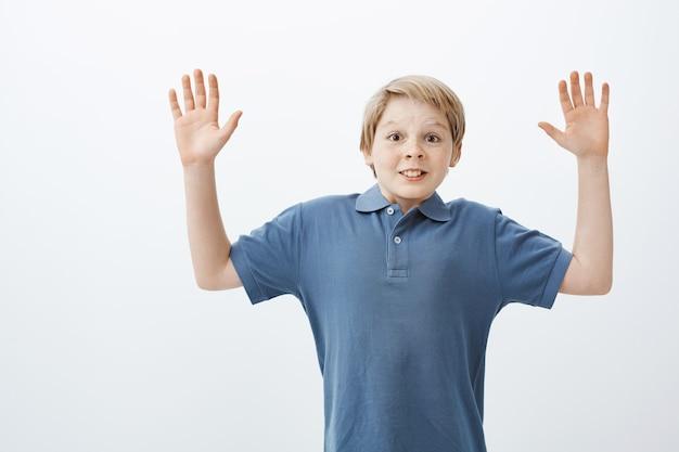Portret van positieve gelukkige tiener in blauw t-shirt verhogen palmen hoog in overgave wordt verrast en gevangen door vriend tijdens het spelen in de tuin