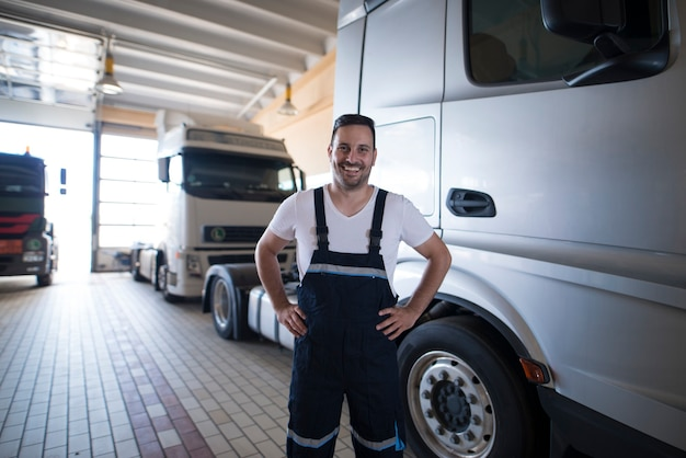 Portret van positieve glimlachende vrachtwagendienstman die zich door vrachtwagenvoertuig in werkplaats bevindt