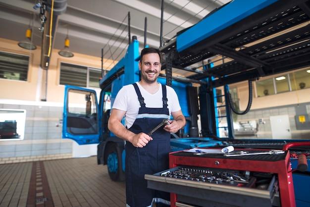 Portret van positieve glimlachende vrachtwagendienstman met hulpmiddelen die zich door vrachtwagenvoertuig in werkplaats bevinden