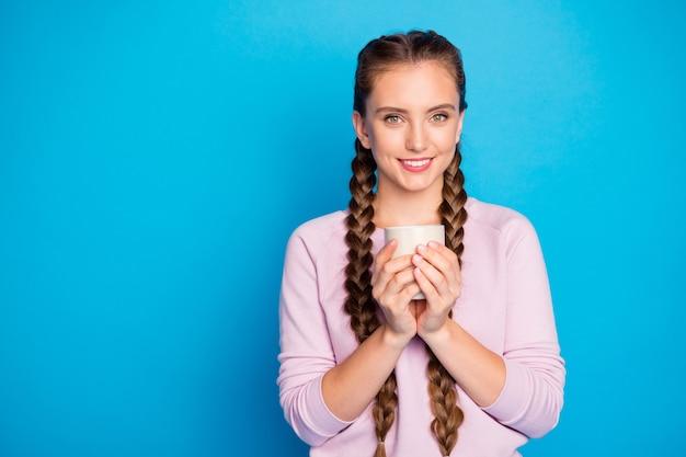 Portret van positieve inhoud duizendjarige meisje houdt warme cappuccino geniet van lente weekenden voel kalm vredige emoties dragen casual stijl outfit geïsoleerd over glans kleur achtergrond