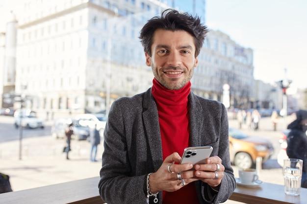 Portret van positieve jonge aantrekkelijke bruinharige man met trendy kapsel glimlachend vrolijk op camera en smartphone in opgeheven handen houden, vrienden te wachten na het werk op zomerterras