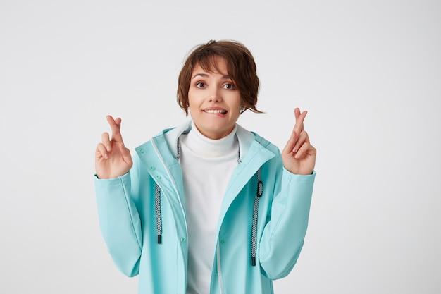 Portret van positieve jonge aardige dame in blauwe regenjas, kijkt naar de camera met gelukkige uitdrukkingen, met gekruiste vingers en gesloten ogen, hoopt op geluk en lip bijt, staat over witte muur.