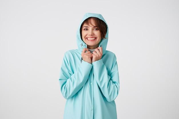 Portret van positieve jonge aardige dame in blauwe regenjas, met een kap op zijn hoofd, kijkt naar de camera met blije uitdrukkingen, breed lachend over witte muur.