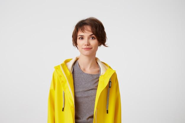 Portret van positieve jonge aardige dame in gele regenjas, geniet van het leven, kijkt naar de camera met gelukkige uitdrukkingen, glimlachend op witte achtergrond.
